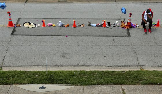 """A man who declined to be identified unfolded a metal chair in the middle of Canfield Drive at a rebuilt memorial to Michael Brown, Jr., preparing to guard it through the night on Thursday, Aug. 8, 2019, before the fifth anniversary of Brown's fatal shooting. """"These are our streets,"""" he said. The Missouri town of Ferguson has seen dramatic change since Brown, a black and unarmed 18-year-old, was killed by white police officer Darren Wilson on Aug. 9, 2014. (Robert Cohen/St. Louis Post-Dispatch via AP)"""