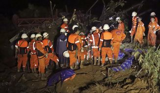 In this Aug. 9, 2019, photo, members of a Myanmar rescue team gather at the landslide-hit area at a village in Paung township, Mon State, Myanmar. A landslide has buried more than a dozen village houses in southeastern Myanmar. (AP Photo)
