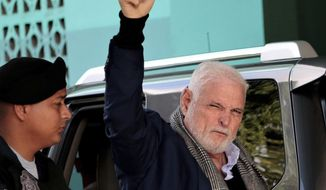 Panama's former President Ricardo Martinelli arrives at court, escorted by a police officer, to continue facing his trail for illegal wiretaps, in Panama City, Thursday, Aug. 8, 2019. (AP Photo/Eric Batista)