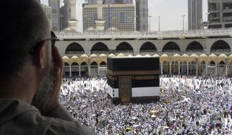 A Muslim pilgrim prays as he watches thousands of pilgrims circumambulate around the Kaaba, the cubic building at the Grand Mosque, ahead of the Hajj pilgrimage in the Muslim holy city of Mecca, Saudi Arabia, Thursday, Aug. 8, 2019. Hundreds of thousands of Muslims have arrived in the kingdom to participate in the annual hajj pilgrimage, which starts Saturday, a ritual required of all able-bodied Muslims at least once in their life. (AP Photo/Amr Nabil)