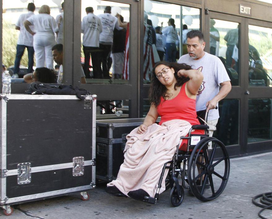"""Jessica Coca Garcia is wheeled away after speaking at League of United Latin American Citizens' """"March For a United America,"""" in El Paso, Texas, on Saturday, Aug. 8, 2019, a week after she and her husband were injured by bullets during a mass shooting. More than 100 people marched through the Texas border denouncing racism and calling for stronger gun laws one week after several people were killed in a mass shooting that authorities say was carried out by a man targeting Mexicans.  (AP Photo/Cedar Attanasio)"""