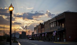 FILE-In this Sunday, Aug. 23, 2015 file photo, the sun rises behind Main Street in the hometown of former President Jimmy Carter in Plains, Ga. Former President Jimmy Carter's home county in rural south Georgia has been embroiled in a costly voting rights lawsuit that experts say could soon be replicated nationwide.(AP Photo/David Goldman)