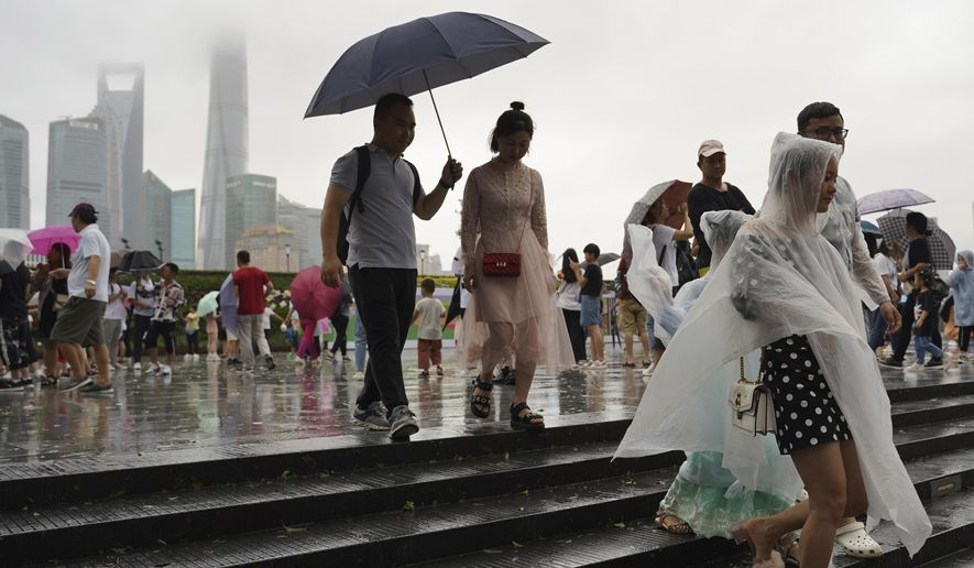 Visitors leave from the bund as Typhoon Lekima approaches in Shanghai Saturday, Aug. 10, 2019. Typhoon Lekima has struck China's coast south of Shanghai, knocking down trees and forcing airlines to cancel flights. (AP Photo/Erika Kinetz)