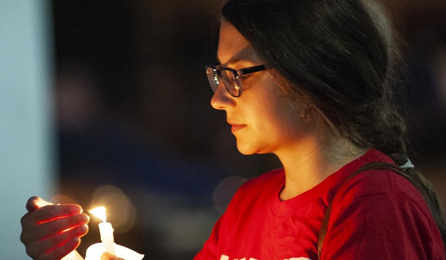 Hannah Gliemann shields her candle from the wind during an Interfaith Vigil for El Paso, Texas, and Dayton, Ohio, mass shooting victims hosted by the Jonesboro local group of the Arkansas Chapter of Moms Demand Action, Thursday, Aug. 8, 2019, at the Craighead County Courthouse in Jonesboro, Ark. The vigil featured speakers from several religious and non-religious groups, a 100-seconds of silence and the lighting of candles to honor the victims of gun violence across the United States. (Quentin Winstine/The Jonesboro Sun via AP)