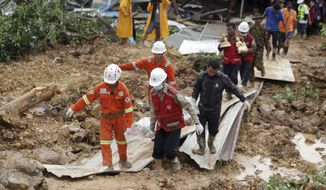 Members of a Myanmar rescue team carry a body at a landslide-hit area in Paung township, Mon State, Myanmar Saturday, Aug. 10, 2019. A landslide has buried more than a dozen village houses in southeastern Myanmar. (AP Photo)