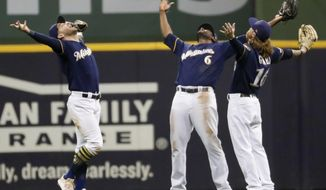 Milwaukee Brewers' Ryan Braun, Lorenzo Cain and Ben Gamel celebrate after a baseball game against the Texas Rangers Saturday, Aug. 10, 2019, in Milwaukee. The Brewers won 3-2. (AP Photo/Morry Gash)