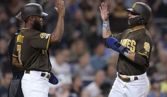 San Diego Padres' Manuel Margot, left, and Luis Urias celebrate after scoring on a double by Fernando Tatis Jr. during the third inning of the team's baseball game against the Colorado Rockies on Friday, Aug. 9, 2019, in San Diego. (AP Photo/Orlando Ramirez)
