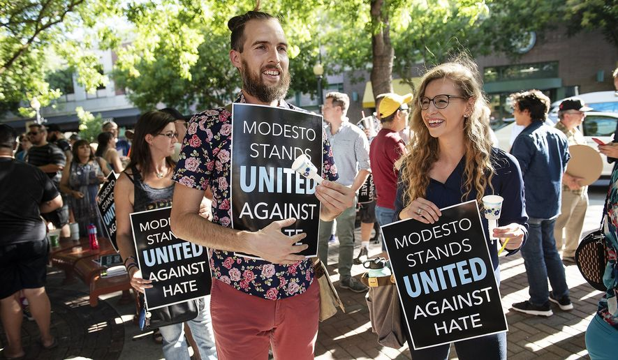 In this Wednesday, Aug. 7, 2019, photo Shaun Gepley, left, and Katy Forney, attend a rally to show their opposition to a straight pride rally planned for Graceada Park in Modesto, Calif. Dozens of people gathered before the Modesto City Council meeting at 10th Street Place in Modesto, Calif. (Andy Alfaro/The Modesto Bee via AP)