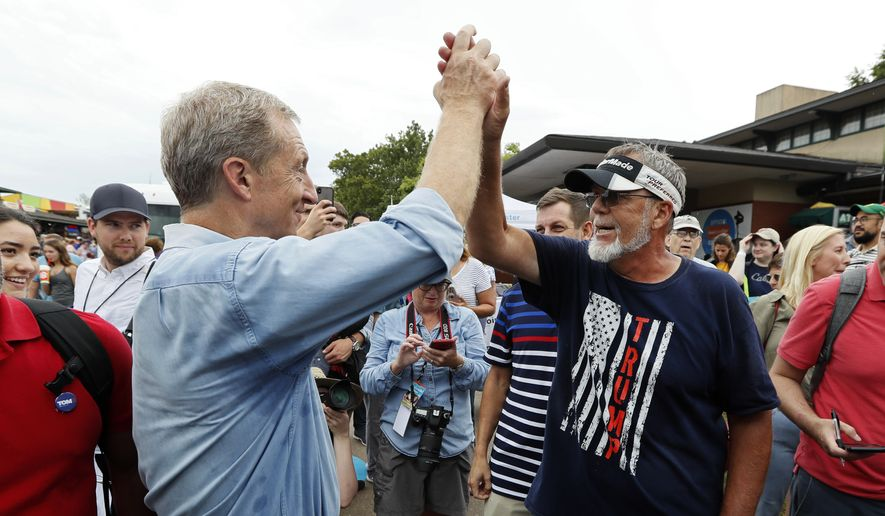 Democratic presidential candidate and businessman Tom Steyer, left, gets a high five from Jim Tangeman, of Monroe, Iowa, before speaking at the Des Moines Register Soapbox during a visit to the Iowa State Fair, Sunday, Aug. 11, 2019, in Des Moines, Iowa. (AP Photo/Charlie Neibergall)