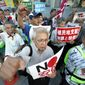 """Protesters with """"No, Abe!"""" signs chat slogans during a rally outside Japanese Prime Minister Shinzo Abe's residence in Tokyo Thursday, Aug. 8, 2019. More than 100 people staged a rally to urge the government to reverse the recent downgrading of South Korea's trade status and to apologize for wartime atrocities in an effort fix rapidly souring relations. (AP Photo/Eugene Hoshiko)"""
