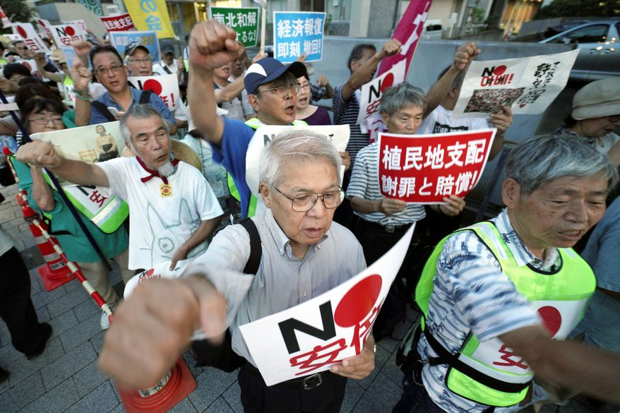 "Protesters with ""No, Abe!"" signs chat slogans during a rally outside Japanese Prime Minister Shinzo Abe's residence in Tokyo Thursday, Aug. 8, 2019. More than 100 people staged a rally to urge the government to reverse the recent downgrading of South Korea's trade status and to apologize for wartime atrocities in an effort fix rapidly souring relations. (AP Photo/Eugene Hoshiko)"