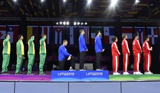 "In this Friday, Aug. 9, 2019 photo, released by Lima 2019 News Services, Race Imboden of the United States takes a knee, as teammates Mick Itkin and Gerek Meinhardt stand on the podium after winning the gold medal in team's foil, at the Pan American Games in Lima, Peru. ""Racism, gun control, mistreatment of immigrants, and a president who spreads hate are at the top of a long list"" of America's problems, Imboden said in a tweet sent after his medals ceremony. ""I chose to sacrifice my moment today at the top of the podium to call attention to issues that I believe need to be addressed. (Jose Sotomayor/Lima 2019 News Services via AP) ** FILE **"