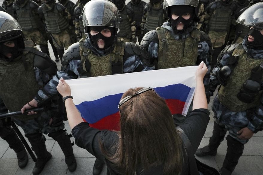 A woman holds a Russian national flag in front of police during a protest in Moscow, Russia, Saturday, Aug. 10, 2019. some thousands of people rallied in central Moscow for the third consecutive weekend to protest the exclusion of opposition and independent candidates from the Russian capital's city council ballot. (AP Photo)