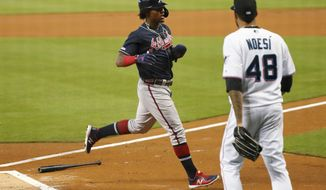 Atlanta Braves' Ronald Acuna Jr., left, crosses home plate to score as Miami Marlins starting pitcher Hector Noesi (48) backs up home plate during the first inning of a baseball game, Sunday, Aug. 11, 2019, in Miami. (AP Photo/Wilfredo Lee)