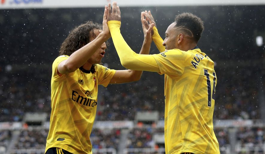 Arsenal's Pierre-Emerick Aubameyang, right, celebrates scoring his side's first goal of the game with team mate Matteo Guendouzi,  during the English Premier League soccer match between Newcastle United and Arsenal, at St James' Park, in Newcastle, England, Sunday, Aug. 11, 2019. (Owen Humphreys/PA via AP)