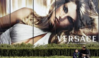 In this Feb. 15, 2008, file photo, a child and a man sit in front of the advertisement of Versace in Shanghai, China. Italian fashion house Versace has apologized in China for selling T-shirts that it said attached incorrect country names to cities, after a Chinese actress said the clothing was suspected of harming the country's territorial integrity and cut her ties with the company.Versace did not identify the T-shirt in a social media post Sunday, Aug. 11, 2019, but Chinese media said the item did not list Hong Kong and Macao as parts of China. Both former European colonies were returned to China in the late 1990s. (AP Photo/Eugene Hoshiko, File)