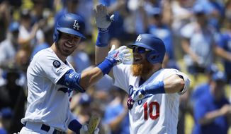 Los Angeles Dodgers' Justin Turner, right, is congratulated by Cody Bellinger after hitting a two-run home run during the first inning of a baseball game against the Arizona Diamondbacks Sunday, Aug. 11, 2019, in Los Angeles. (AP Photo/Mark J. Terrill)