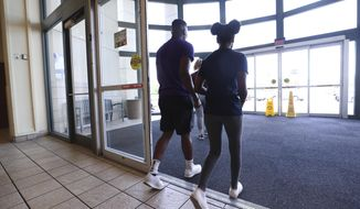 In a  July 26, 2019 photo, Irakoze Chartier, 19, left, and his sister Noela Furaha, 13, leave the Jefferson Mall in Louisville, Ky. after being informed of their Youth Escort Policy. The policy stipulates that anyone under the age of 18 must be accompanied by an adult at least 21 years of age after 4pm on the weekends.  (Sam Upshaw Jr/Courier Journal via AP)