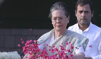FILE-In this May 21, 2019 file photo, United Progressive Alliance Chairperson Sonia Gandhi, center, with her son and the then Congress Party President Rahul Gandhi, pays homage to former Indian prime minister Rajiv Gandhi on his death anniversary in New Delhi, India. Sonia Gandhi took back the reins of the party from her son Rahul on Saturday. She'll be interim president until the party elects a new leader. (AP Photo/Manish Swarup, File)