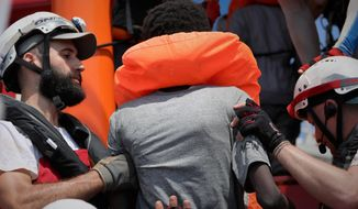 In this photo taken Saturday and released Sunday, Aug. 11, 2019, a rescue team of the Ocean Viking ship, operated by the NGOs Sos Mediterranee and Doctors Without Borders, helps a person rescued from a rubber dinghy with over 80 migrants off the Libyan coast. The Ocean Viking was already carrying over 80 people rescued earlier, and is blocked at sea while it waits to be assigned a safe port. Italian Interior Minister Matteo Salvini, who has triggered a government crisis in Italy, signed Friday a ban on the ship's entry into Italian waters. (Hannah Wallace Bowman/MSF/Sos Mediterranee via AP)