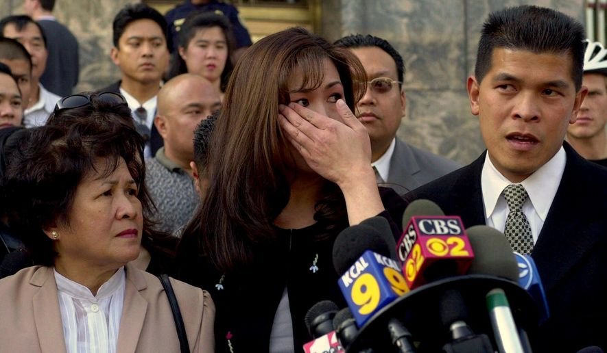 FILE - In this March 26, 2001, file photo, Lilian Santos Ileto, left, the mother of slain Filipino American postal worker Joseph Ileto,  with his sister, Deena, wiping tears from her eyes, and brother Ismael talk with reporters in front of the Los Angeles Federal Court after Buford O. Furrow, was sentenced to two life sentences plus 110 years in prison for the crime and the wounding of five people at a Jewish Community center. A moment of silence marked the day 20 years ago when Furrow, a white-supremacist gunman wounded children and staff at a Los Angeles Jewish center before killing Ileto. The Los Angeles Times reports family and friends of victims were on hand outside a U.S. Post Office where a plaque commemorates Ileto, who was gunned down Aug. 10, 1999. His brother, Ismael Ileto, called for stricter gun control laws, citing the rise in mass shootings. (AP Photo/Nick Ut, File)