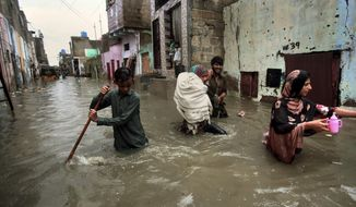 A family wades through a flooded street caused by heavy monsoon rains, in Karachi, Pakistan, Sunday, Aug. 11, 2019. Monsoon rains have inundated much of Pakistan, leaving large parts of the southern city of Karachi underwater and causing some deaths. (AP Photo/Fareed Khan)