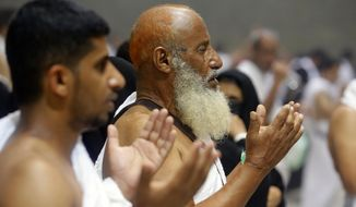 """Muslim pilgrims pray after they cast stones at a pillar symbolizing the stoning of Satan, in a ritual called """"Jamarat,"""" the last rite of the annual hajj, on the first day of Eid al-Adha, in Mina near the holy city of Mecca, Saudi Arabia, Sunday, Aug. 11, 2019. The hajj is required of all Muslims to perform once in their lifetime if they are financially and physically able. (AP Photo/Amr Nabil)"""
