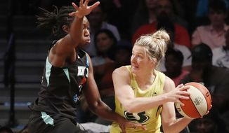 Seattle Storm guard Sami Whitcomb, right, passes around New York Liberty center Tina Charles, left, during the first half of a WNBA basketball game, Sunday, Aug. 11, 2019, in New York. (AP Photo/Kathy Willens)
