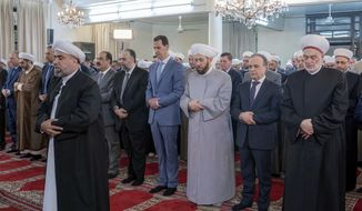 In this photo released by the Syrian official news agency SANA, Syrian President Bashar Assad, forth right, prays on the first day of the the Eid al-Adha, at Afram Mosque in Damascus, Syria, Sunday, Aug. 11, 2019. State news agency SANA showed Assad attending the payers early Sunday at Afram Mosque along with top officials including the prime minister and the country's grand mufti. (SANA via AP)