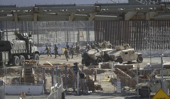 U.S. military personnel deploy at the San Ysidro port of entry in San Diego on Sunday, Nov. 25, 2018. The Border Patrol office in San Diego said via Twitter that pedestrian crossings have been suspended at the San Ysidro port of entry at both the East and West facilities. All northbound and southbound traffic was halted. (AP Photo/Greg Bull)