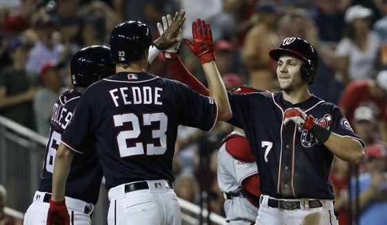 Washington Nationals' Trea Turner, right, celebrates after bringing home Victor Robles, left, and Erick Fedde  (23) during the fourth inning of a baseball game against the Cincinnati Reds at Nationals Park, Monday, Aug. 12, 2019, in Washington. (AP Photo/Alex Brandon)