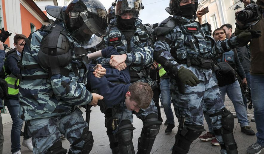 Police detain a protester during a protest in Moscow, Russia, Saturday, Aug. 10, 2019. Tens of thousands of people rallied in central Moscow for the third consecutive weekend to protest the exclusion of opposition and independent candidates from the Russian capital's city council ballot. (AP Photo)