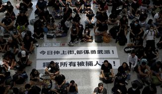 "THIS ADDS TO CLARIFY THE TRANSLATION - Protesters surround banners that read: ""Those on the street today are all warriors!"" top, and ""Release all the detainees!"" during a sit-in rally at the arrival hall of the Hong Kong International airport, Monday, Aug. 12, 2019. Hong Kong police showed off water cannons Monday as pro-democracy street protests stretched into their 10th week with no sign of either side backing down. (AP Photo/Vincent Thian)"