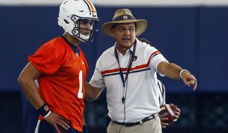 FILE - In this Aug. 2, 2019, file photo, quarterback Joey Gatewood gets some instruction from coach Gus Malzahn during Auburn NCAA college football practice in Auburn, Ala. Malzahn is banking on his own his play calling abilities and a freshman quarterback to carry the Tigers through a difficult schedule. (AP Photo/Butch Dill, File)