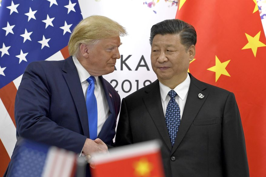 In this  June 29, 2019, photo, U.S. President Donald Trump, left, shakes hands with Chinese President Xi Jinping during a meeting on the sidelines of the G-20 summit in Osaka, western Japan. (AP Photo/Susan Walsh) **FILE**