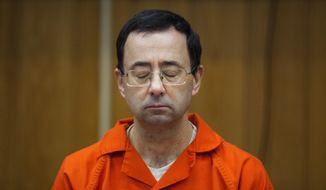 FILE - In this Feb. 5, 2018, file photo, Larry Nassar listens during his sentencing at Eaton County Circuit Court in Charlotte, Mich. Michigan State University has agreed to improve its processes for investigating sexual misconduct complaints, to institute a new chaperone policy for sensitive medical exams and to take other steps to resolve a federal civil rights investigation related to Nassar's abuse. The agreement was announced Monday, Aug. 12, 2019 by the U.S. Department of Health and Human Services' Office for Civil Rights. (Cory Morse/The Grand Rapids Press via AP, File)