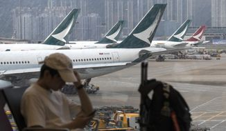 "A man checks his smartphone while Cathay Pacific Airways planes park at the Hong Kong International Airport on Monday, Aug. 12, 2019. The chief executive of Hong Kong's Cathay Pacific Airways said Monday there will be ""disciplinary consequences"" for employees involved in ""illegal protests,"" as the airline joins a slate of businesses that have appeased and apologized to China in recent days over political flaps. (AP Photo/Vincent Thian)"