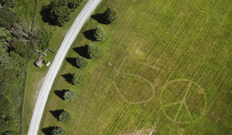 This Wednesday, July 24, 2019, file photo shows the number 50 and a peace sign mowed into the grass at the site of the 1969 Woodstock Music and Arts Fair in Bethel, N.Y. Fifty years later, memories of the rainy weekend Aug. 15-18, 1969, remain sharp among people who were in the crowd and on the stage. (AP Photo/Seth Wenig)