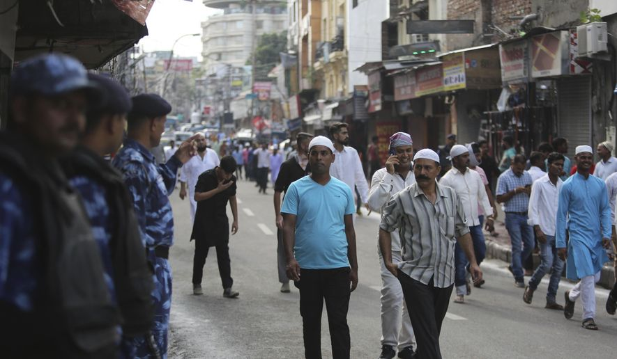 Muslims walk past Indian paramilitary soldiers after offering prayers during Eid al-Adha, or the Feast of the Sacrifice, in Jammu, India, Monday, Aug.12, 2019. An uneasy calm prevailed in Indian-administered Kashmir on Monday as people celebrated a major Islamic festival during a severe crackdown after India moved to strip the disputed region of its constitutional autonomy and imposed an indefinite curfew. (AP Photo/Channi Anand)
