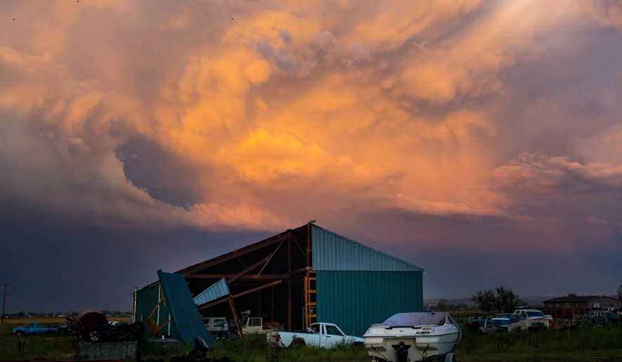 In this Sunday, Aug. 11, 2019 photo a large shed along 12 Mile Road between Shepherd and Billings, Mont. shows significant damage after a hailstorm and strong winds. (Mike Clark/ Billings Gazette via AP)