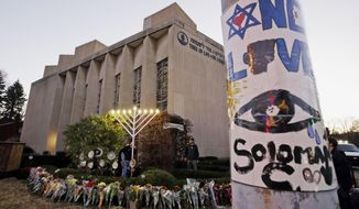 FILE - This Dec. 2, 2018, file photo shows a menorah at a memorial outside the Tree of Life Synagogue, where Robert Bowers killed worshippers in an Oct. 27 shooting, as people prepare for a celebration service at sundown on the first night of Hanukkah in the Squirrel Hill neighborhood of Pittsburgh. Bowers, charged with killing 11 worshippers at the Pittsburgh synagogue last year, has a court hearing Monday, Aug. 12, 2019. Prosecutors have not made a final decision on whether to seek the death penalty. Bowers is not expected to be in court.  (AP Photo/Gene J. Puskar, File)
