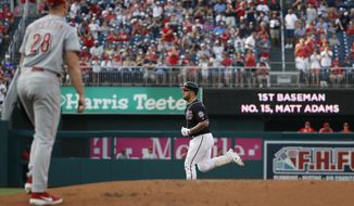 Washington Nationals' Matt Adams, back center, rounds the bases for his two-run home run as Cincinnati Reds starting pitcher Anthony DeSclafani (28) walks back to the mound during the first inning of a baseball game at Nationals Park, Monday, Aug. 12, 2019, in Washington. (AP Photo/Alex Brandon)