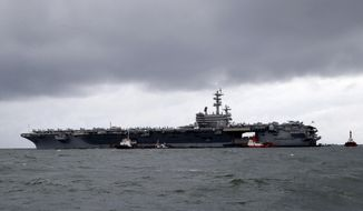 In this Aug. 7, 2019, file photo, rain clouds loom over the U.S. aircraft carrier USS Ronald Reagan as it is anchored off Manila Bay, Philippines for a port call. (AP Photo/Bullit Marquez, File)