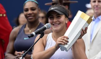 Canada's Bianca Andreescu holds the winner's trophy as Serena Williams of the USA looks on after Williams had to retire from the final of the Rogers Cup tennis tournament in Toronto on Sunday, Aug. 11, 2019. (Frank Gunn/The Canadian Press via AP)