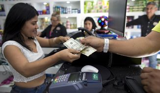 A man pays for his purchases with U.S dollars at a store in Caracas, Venezuela, Friday, Aug. 9, 2019. A number of trendy shops packed with imported consumer goods have popped up in the last few months across Caracas while socialist authorities look the other way as the greenback has replaced the worthless local currency, the bolivar, as an accepted form of payment. (AP Photo/Ariana Cubillos)