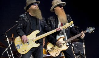FILE - In this June 24, 2016, file photo, Dusty Hill, left, and Billy Gibbons from the rock band ZZ Top perform at the Glastonbury music festival at Worthy Farm, in Somerset, England. Joe Walsh will be joined by ZZ Top, Brad Paisley, Sheryl Crow, and Jason Isbell and The 400 Unit at his VetsAid music festival to benefit veterans.The award-winning musician announced Monday, Aug. 12, 2019, file photo, that tickets for the Nov. 10 concert at the Toyota Center in Houston will go on sale Friday. (Photo by Jonathan Short/Invision/AP, File)
