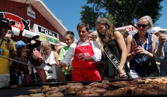 Democratic presidential candidate South Bend Mayor Pete Buttigieg cooks pork at the Iowa State Fair, Tuesday, Aug. 13, 2019, in Des Moines, Iowa. (AP Photo/John Locher)