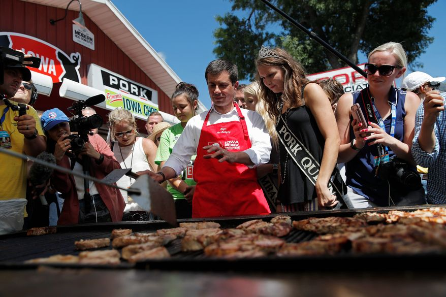 Democratic presidential candidate South Bend Mayor Pete Buttigieg cooks pork at the Iowa State Fair, Tuesday, Aug. 13, 2019, in Des Moines, Iowa. (AP Photo/John Locher)