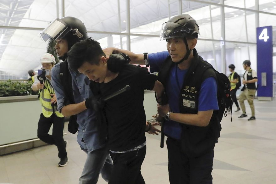 Policemen arrest a protester during a demonstration at the Airport in Hong Kong, Tuesday, Aug. 13, 2019. Chaos has broken out at Hong Kong's airport as riot police moved into the terminal to confront protesters who shut down operations at the busy transport hub for two straight days. (AP Photo/Kin Cheung)