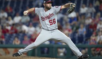 FILE - In this Aug. 28, 2018, file photo, Washington Nationals relief pitcher Greg Holland throws a pitch during the ninth inning of a baseball game against the Philadelphia Phillies, in Philadelphia. A person familiar with the deal tells The Associated Press that right-handed reliever Greg Holland and the Washington Nationals have an agreement in principle on a minor league contract, pending the completion of a successful physical exam. The person confirmed the move to the AP on condition of anonymity Tuesday, Aug. 13, 2019, because nothing had been announced by the team.(AP Photo/Chris Szagola, File)